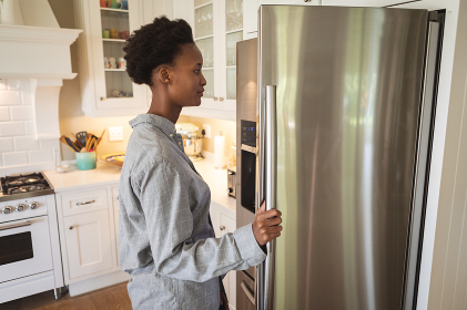 Mixed race woman spending time at home, standing in her kitchen and looking into a refrigerator. Self isolating and social distancing in quarantine lockdown during coronavirus covid 19 epidemic.