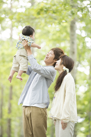 新緑の中で子供をあやす両親