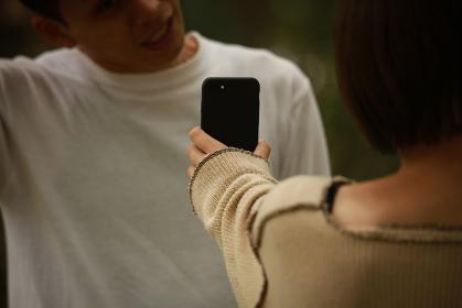 男性にスマートフォンの画面を見せる女性
