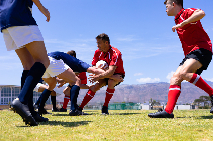 Low angle side view of a group of Caucasian male rugby players from opposing teams wearing team uniforms, in a tackle for possession of the ball on a rugby pitch during a match, with blue sky in the background