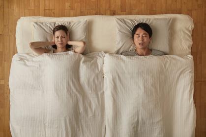夫のいびきがうるさく耳をふさぐ日本人女性