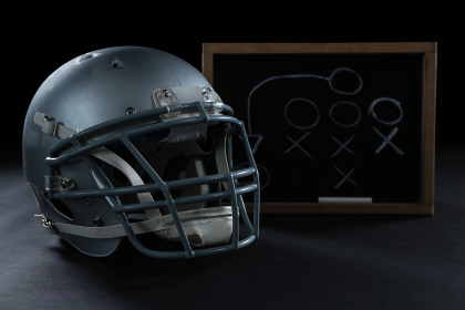Close-up of American football and game strategy drawn on board