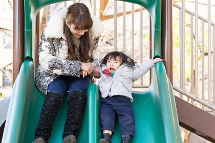 遊具で遊ぶ子ども(女の子・滑り台・表情)