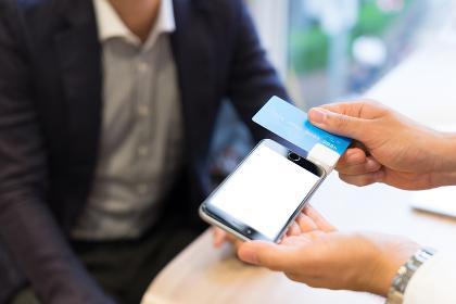 スマートフォンでクレジットカードの決済をする男性