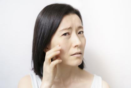 肌のトラブルに悩む中年女性
