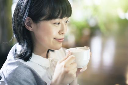 暖かい雰囲気の空間で、コーヒーを飲む若い女性