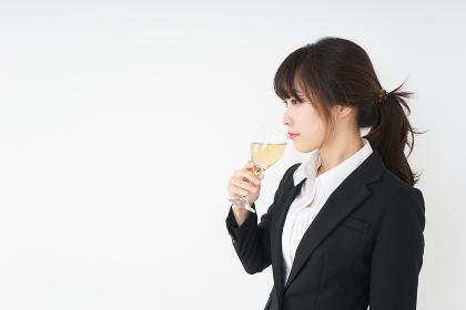 スーツ姿でお酒を飲む若い女性