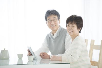 タブレットPCを持ち微笑むシニア夫婦