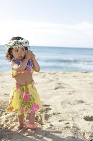 フラダンスの衣装を着て貝殻の音を聞いているハーフの女の子