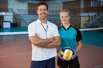 Happy male coach and volleyball player standing in the court