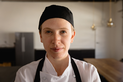Portrait close up of a confident Caucasian woman at a cookery class, wearing chefs whites, a black hat and apron, standing, looking to camera and smiling