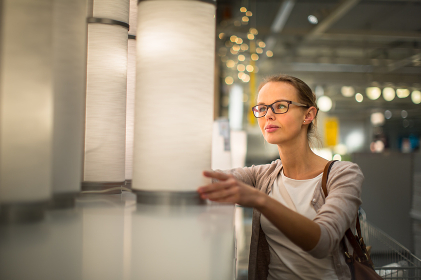 Pretty, young woman choosing the right light for her appartment in a modern home furnishings store (color toned image  shallow DOF)