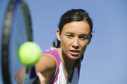 Female Tennis Player Hitting Ball close up of racket focus on player