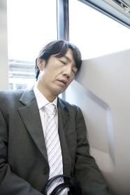 座席に座ってうたた寝するビジネスマン