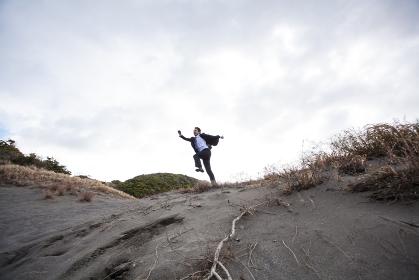 砂丘をジャンプするビジネスマン