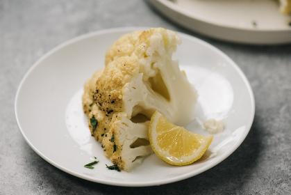 Wedge of whole roasted cauliflower with lemon and parsley