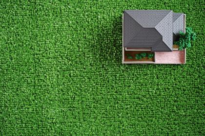 緑の人工芝の右上に置いたミニチュアの家