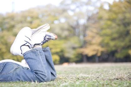 芝生に寝転んだ小学生の足