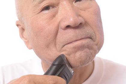 電気シェーバーで髭を剃る日本人シニア男性