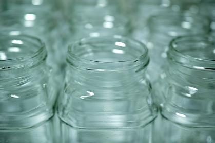 一面に並べたインスタントコーヒーの空き瓶。リサイクルの空き瓶。斜俯瞰撮影の背景素材。