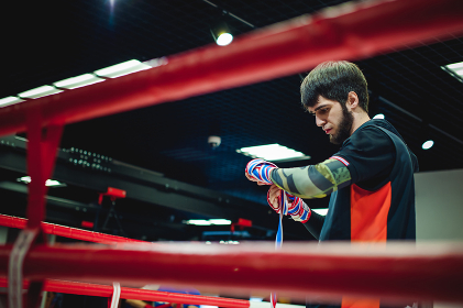 Professional Muay Thai and K1 fighter. Male boxer in training sportswear, an exercise in the sports hall, Preparation Boxing bandage