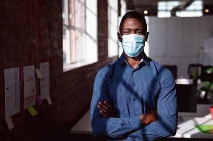 Portrait of african american businessman in face mask standing in office with arms crossed. working in business at a modern office during coronavirus covid 19 pandemic.