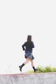 土手の上を走る女子高生