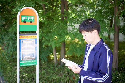 バス停で本を読む男性(読書・時間を潰す)