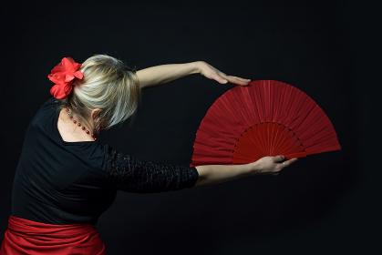 Low Key photo of Flamenco Dancer holding red fan