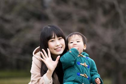 手を振る親子(母親と男の子)