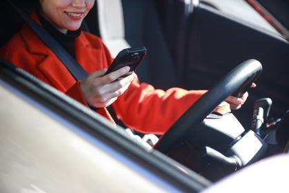 運転しながらスマートフォンの操作をする女性
