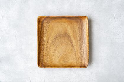 グレーの背景に置かれた木製で四角形の皿