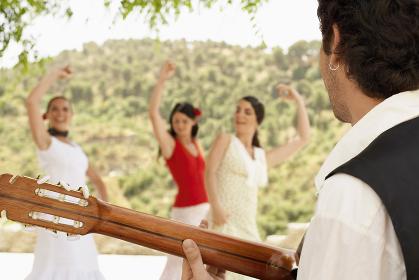 Man Playing Guitar With Women Dancing Flamenco