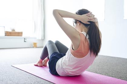 部屋の中でトレーニングをする若い日本人の女性
