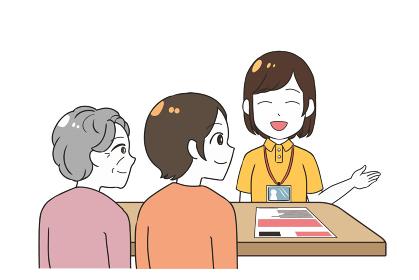 笑顔で説明する女性介護士 祖母と娘 老人ホーム