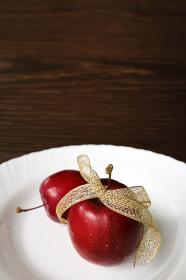 皿の上の金色のリボンで飾った姫リンゴ 6 縦位置