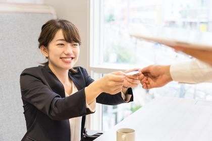 クレジットカードを店員に手渡す女性(決済・支払い・キャッシュレス)