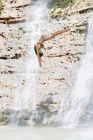 綺麗な水の流れる川で滝のそばで高いところから飛び込むスポーティな黒髪の日本人女性
