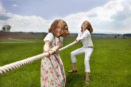 Children pulling a rope in countryside