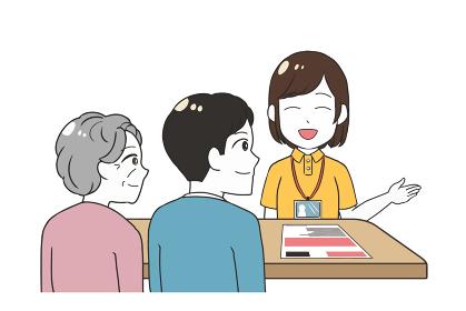 笑顔で説明する女性介護士 祖母と息子 老人ホーム