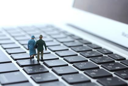 ノートパソコンと人間のミニチュア人形のジオラマ