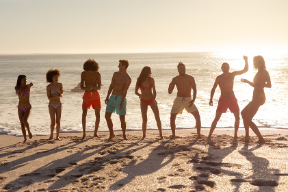 A multi-ethnic group of male and female friends on holiday having fun on a beach, dancing by the sea as the sun goes down behind them