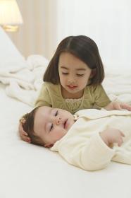 寝室で不機嫌な赤ちゃんをあやす女の子
