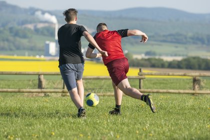 two men playing football on a football field in the green