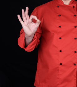 chef in red uniform shows a gesture of approval with his right hand