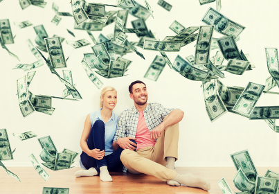 happy couple at home over dollar money falling