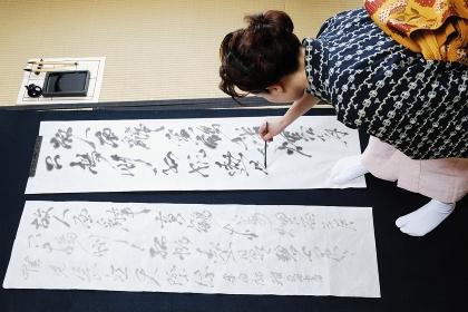 書き初めをする着物を着た女性