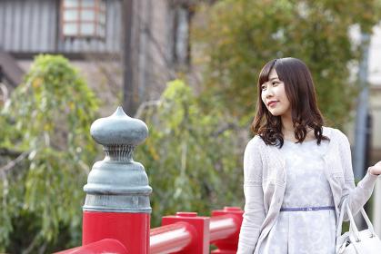 赤い橋を渡る若い日本人女性