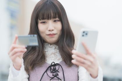 クレジットカードとスマートフォンでネットショッピングをする女性
