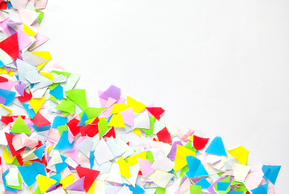 千切った色紙の紙片と白バックのコピースペース